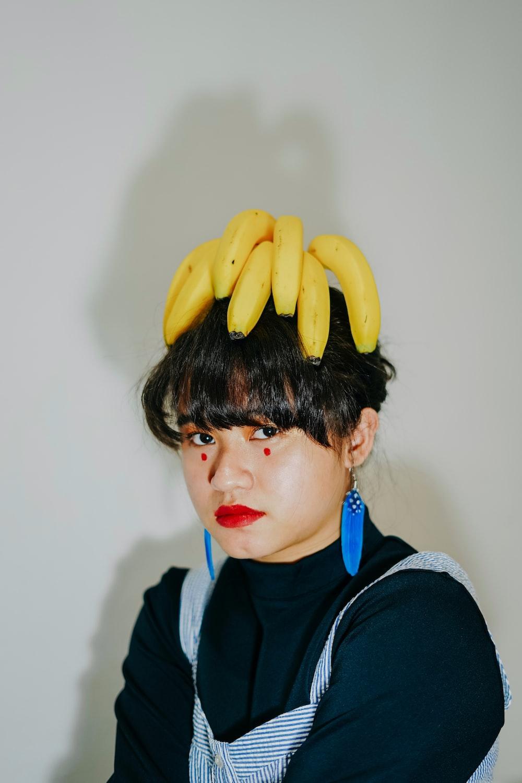 boy in black hoodie holding yellow banana