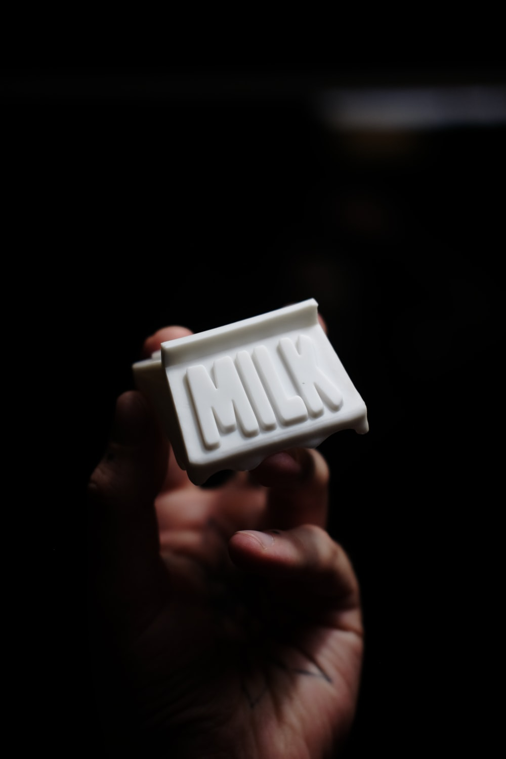 person holding white plastic container