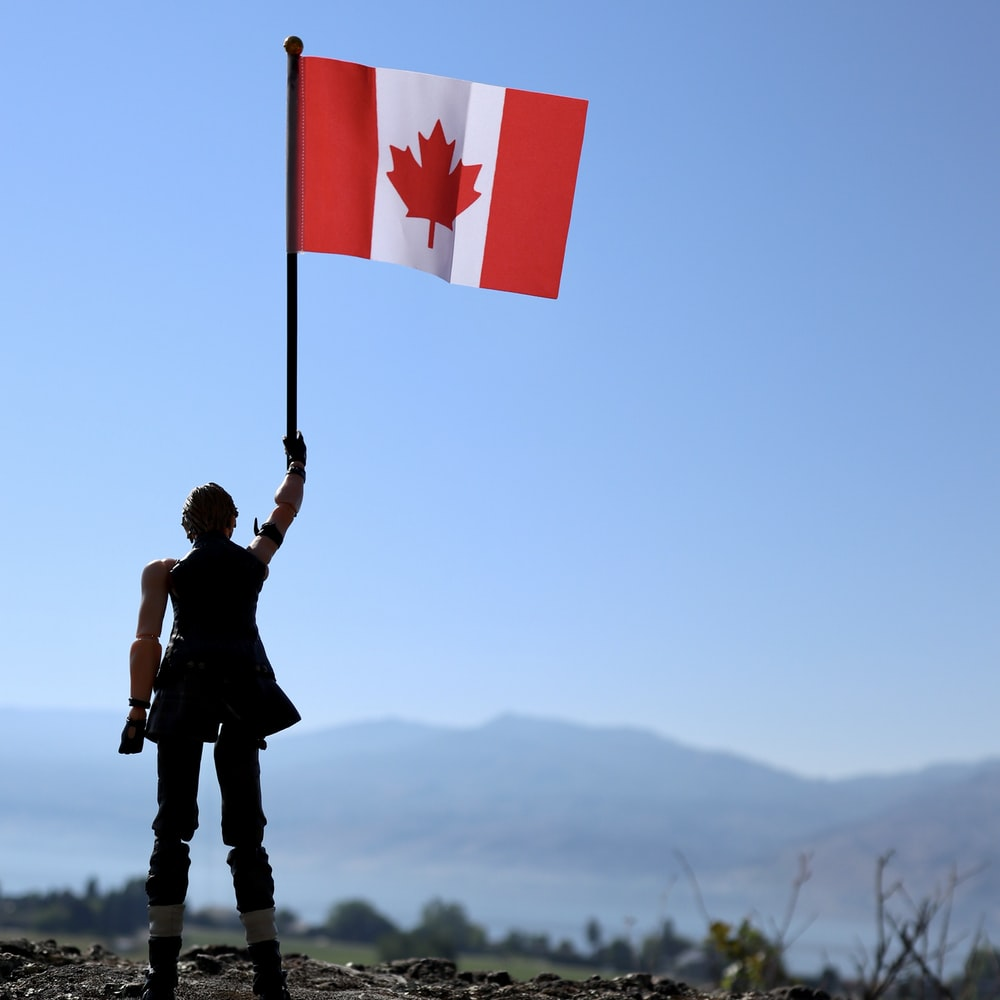 man holding flag of us a standing on rock during daytime