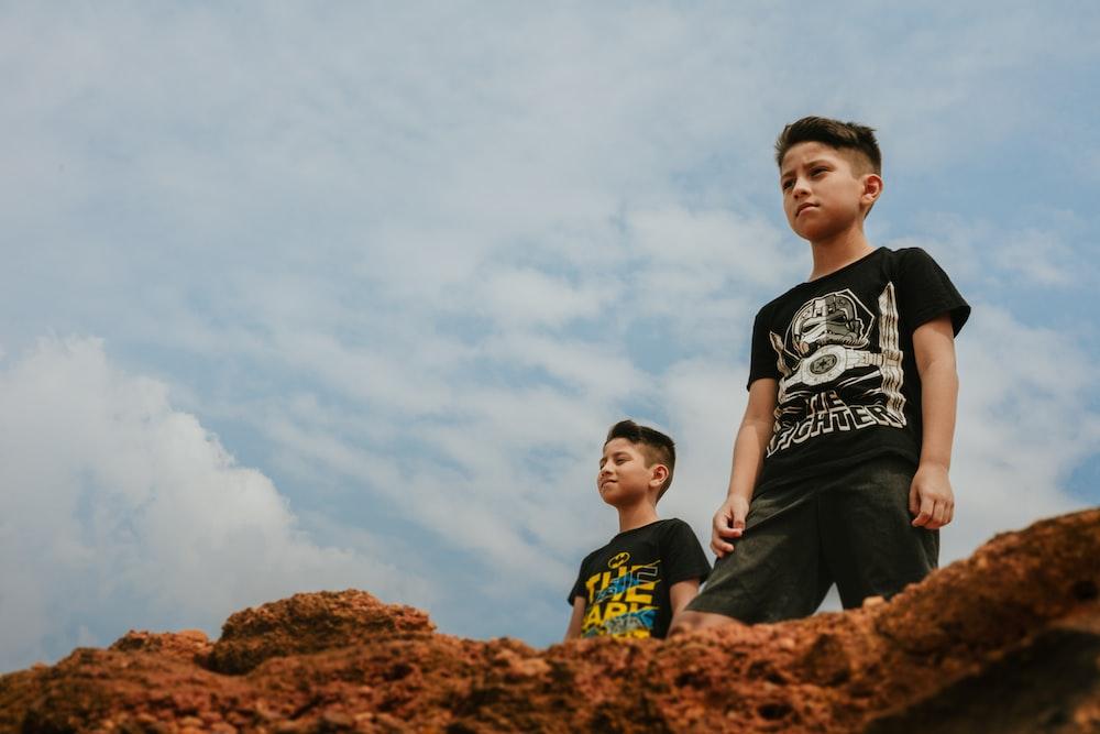 2 men standing on brown rock during daytime