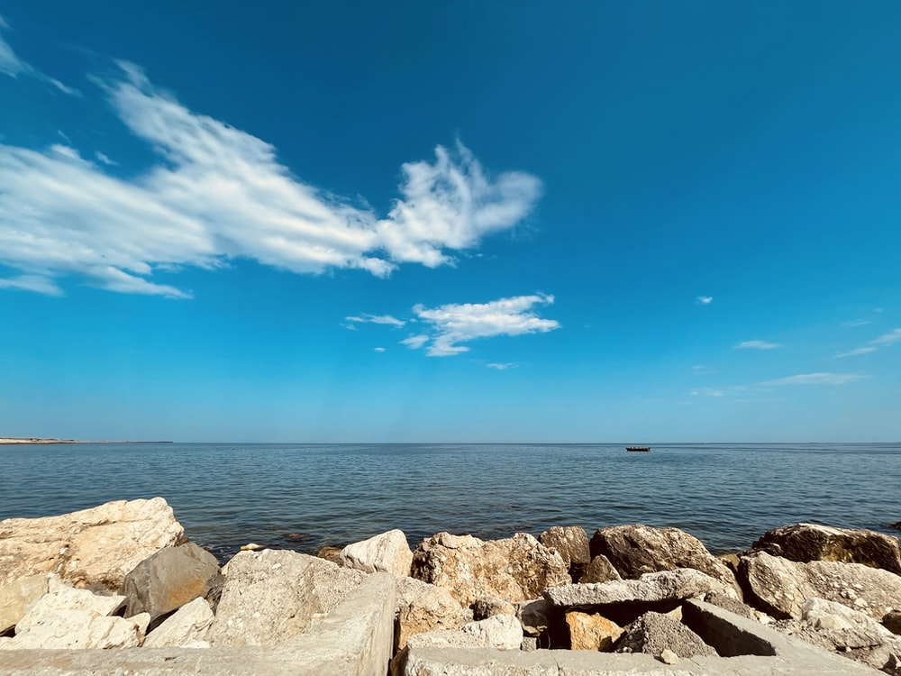 brown rocks near body of water under blue sky during daytime