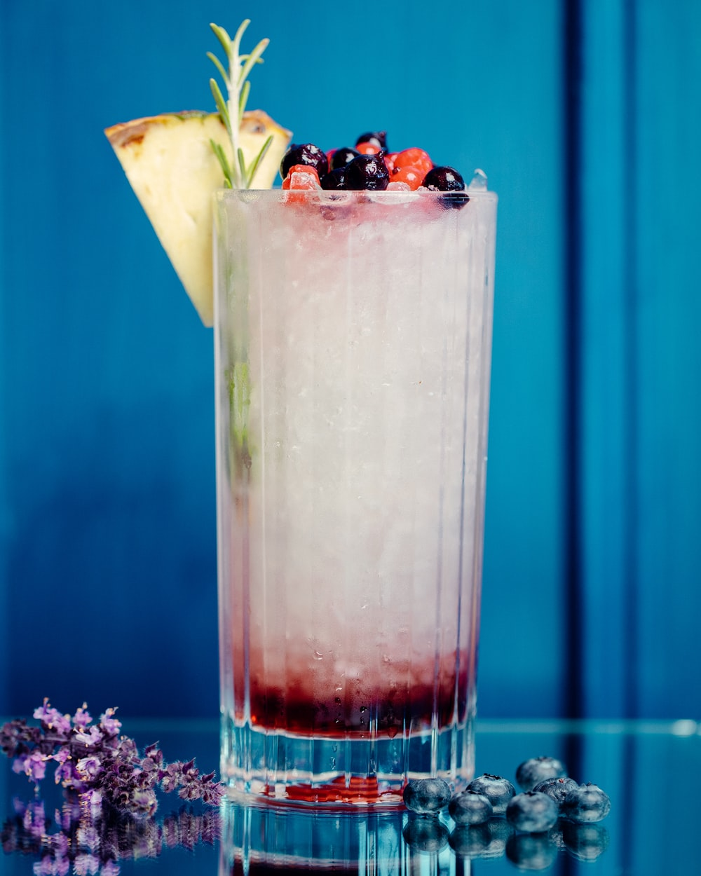 clear drinking glass with ice and black berries
