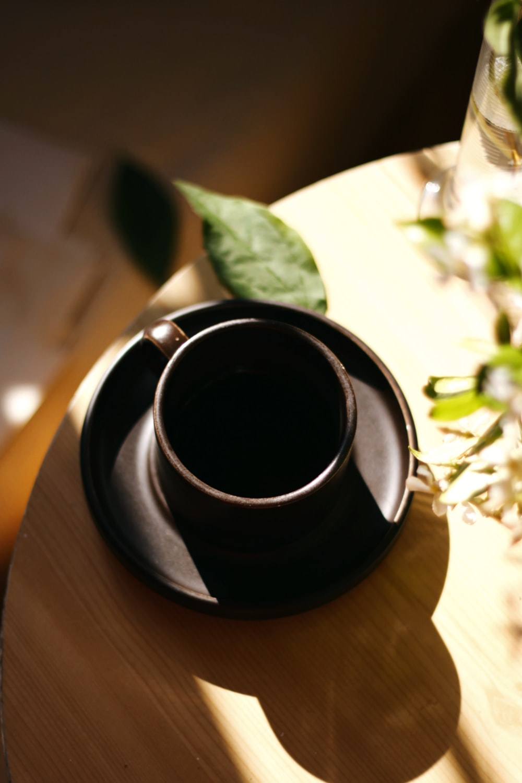 black liquid in black ceramic mug on brown wooden table