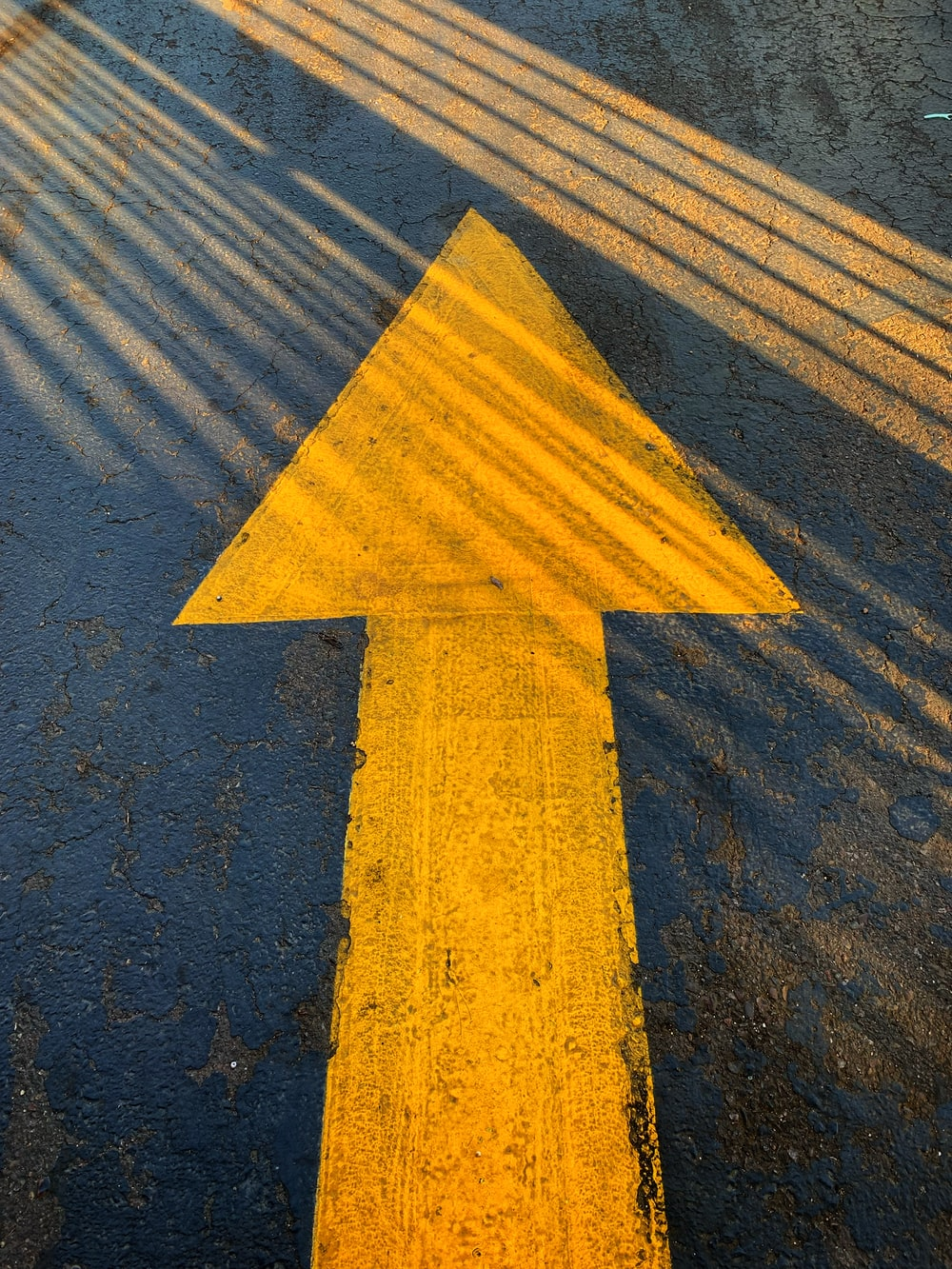 yellow arrow sign on gray concrete road