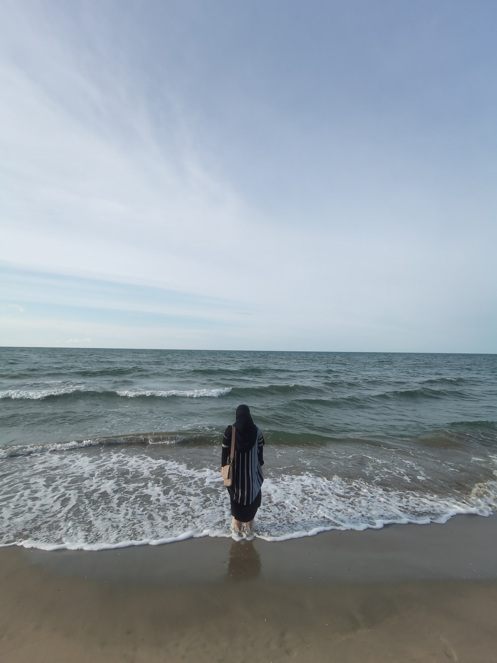 woman in black long sleeve shirt and black pants standing on beach during daytime