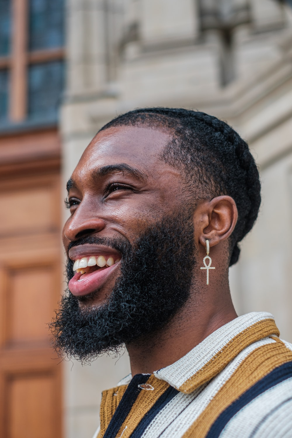 man in white and brown striped shirt smiling