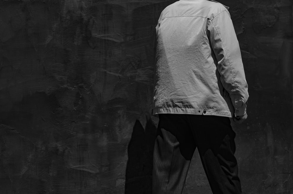 man in white dress shirt and black pants standing beside wall