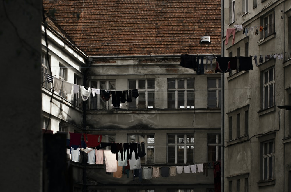 clothes hanged on clothes line in front of brown brick building