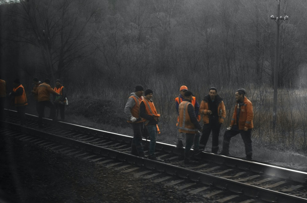 people standing on train rail during daytime