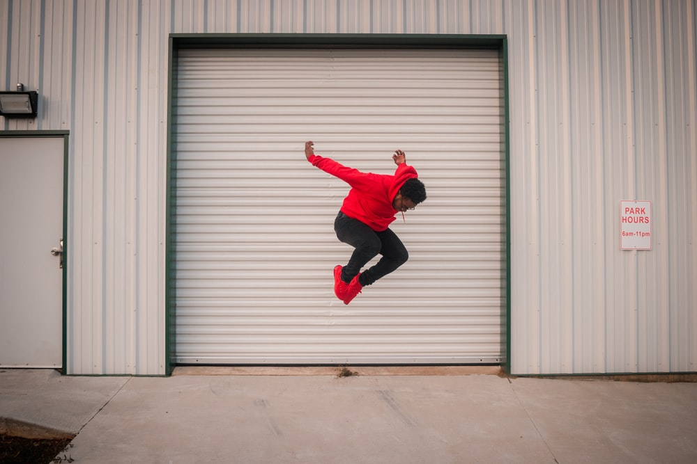 man in red jacket and black pants jumping near white roll up door