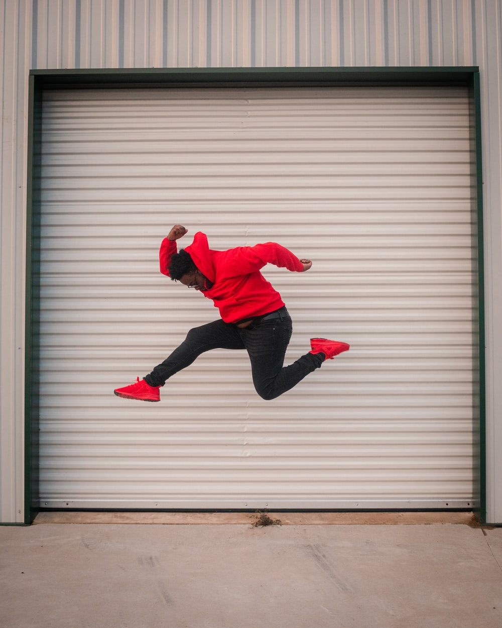 man in red hoodie jumping in front of white roll up door