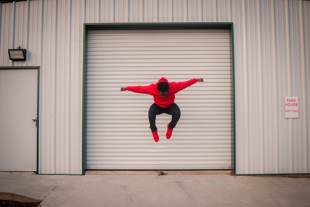 man in red jacket jumping in front of gray roll up door