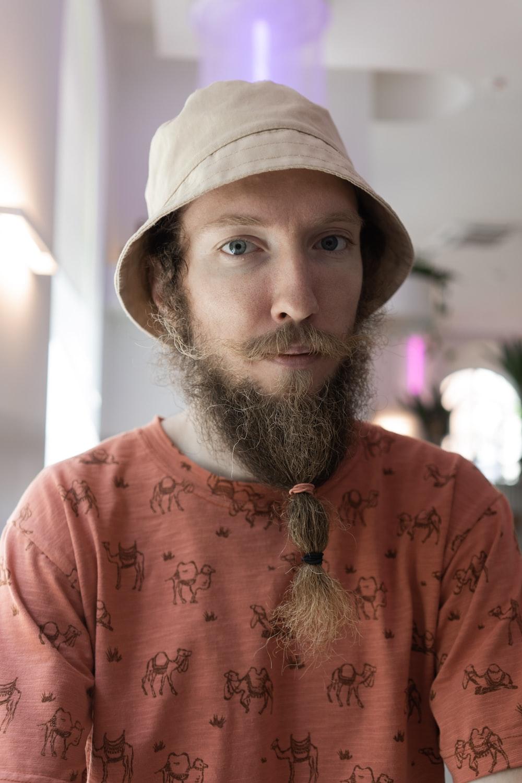 man in orange crew neck shirt wearing brown hat