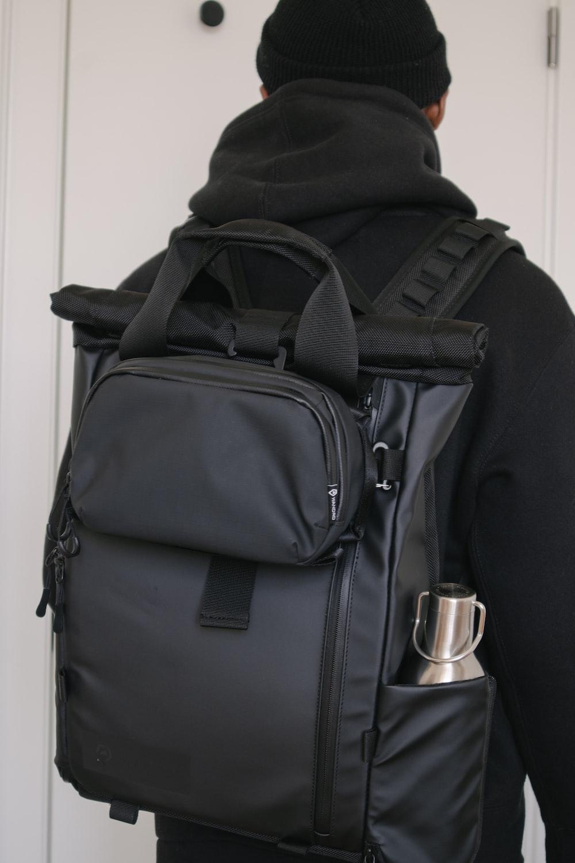 black backpack on white wooden door