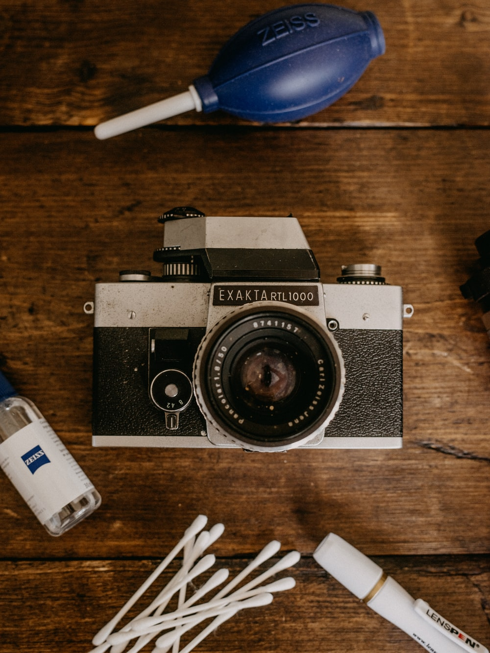 black and silver pentax camera on brown wooden table