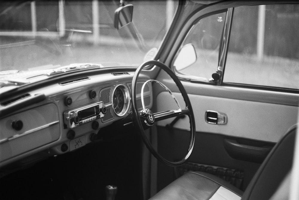 grayscale photo of car steering wheel