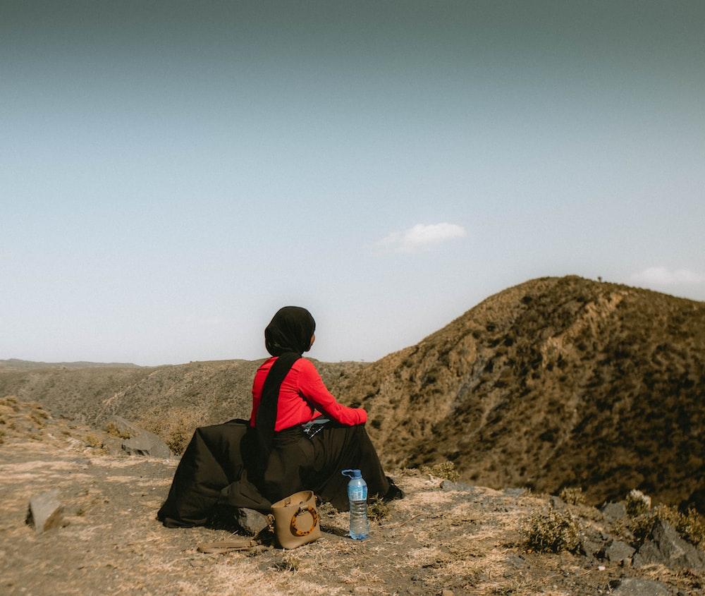 man in black jacket sitting on brown rock during daytime