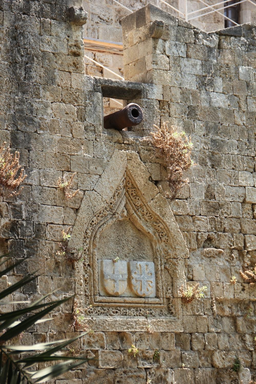 brown wooden cross on brown brick wall