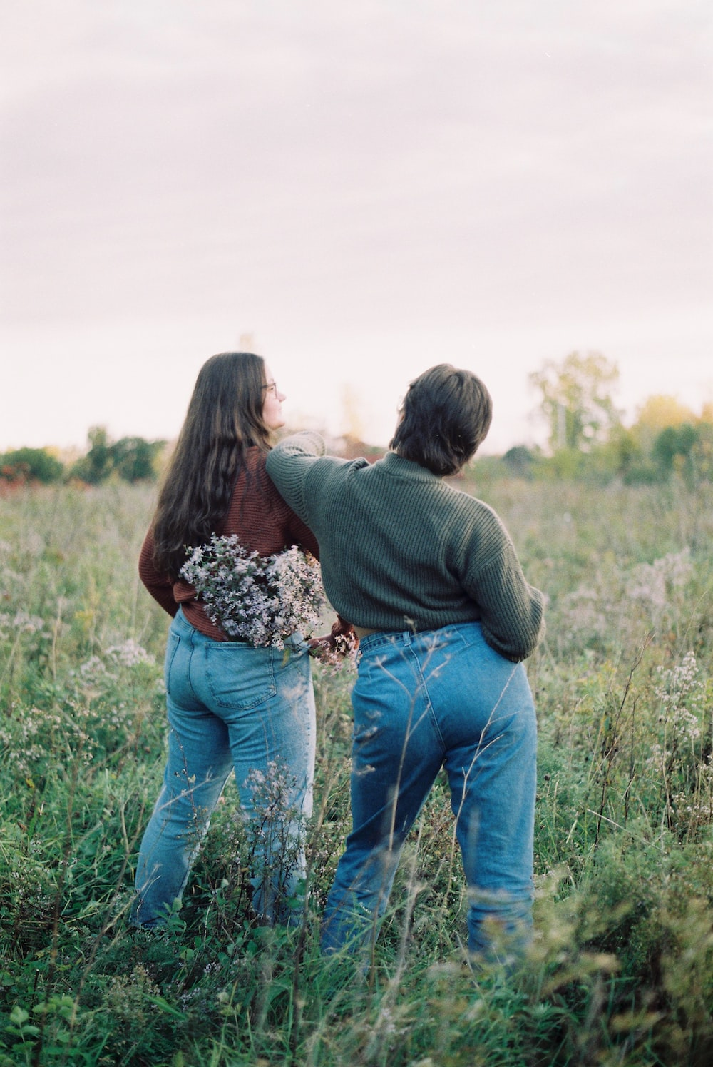 couple kissing on green grass field during daytime