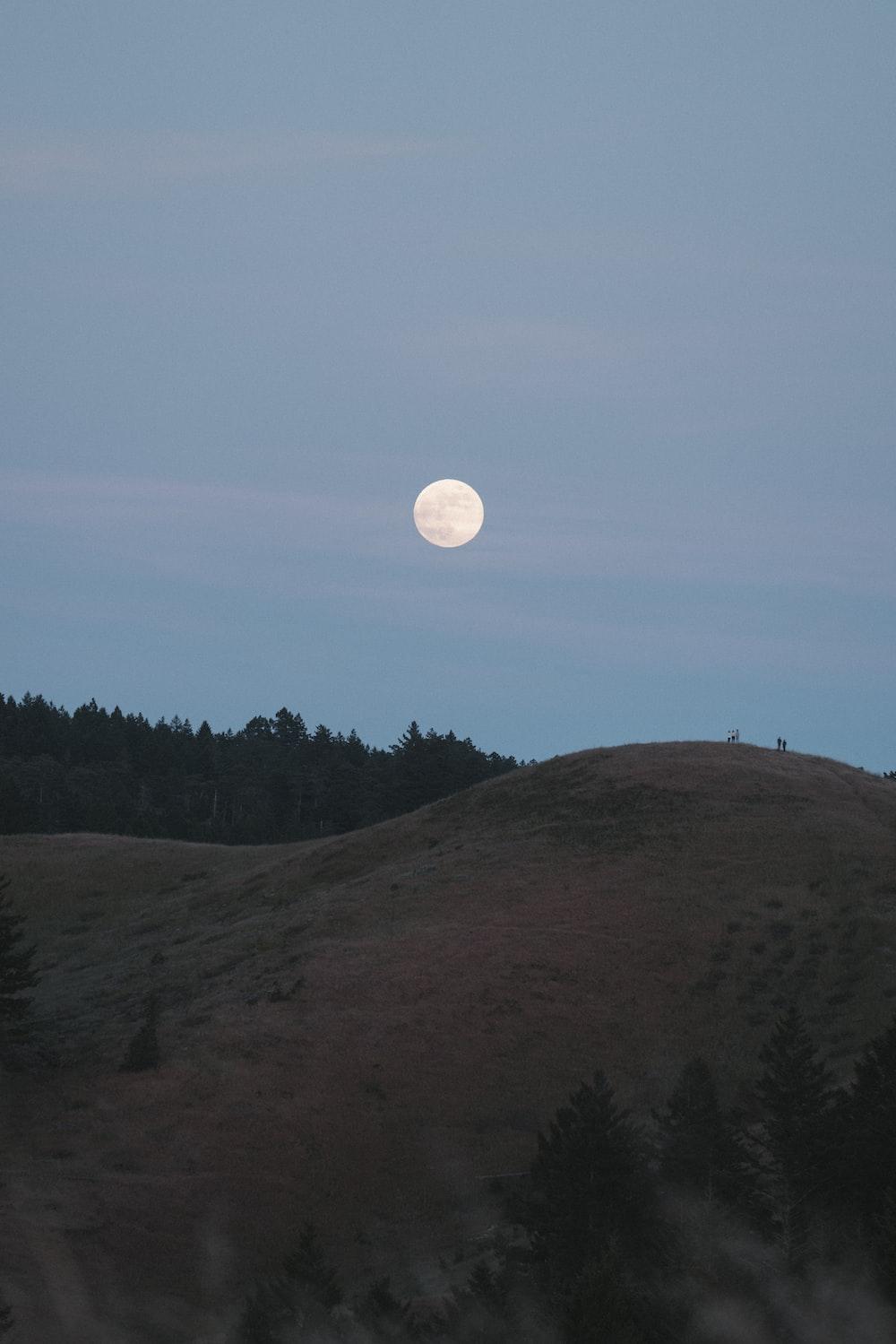 full moon over green mountain