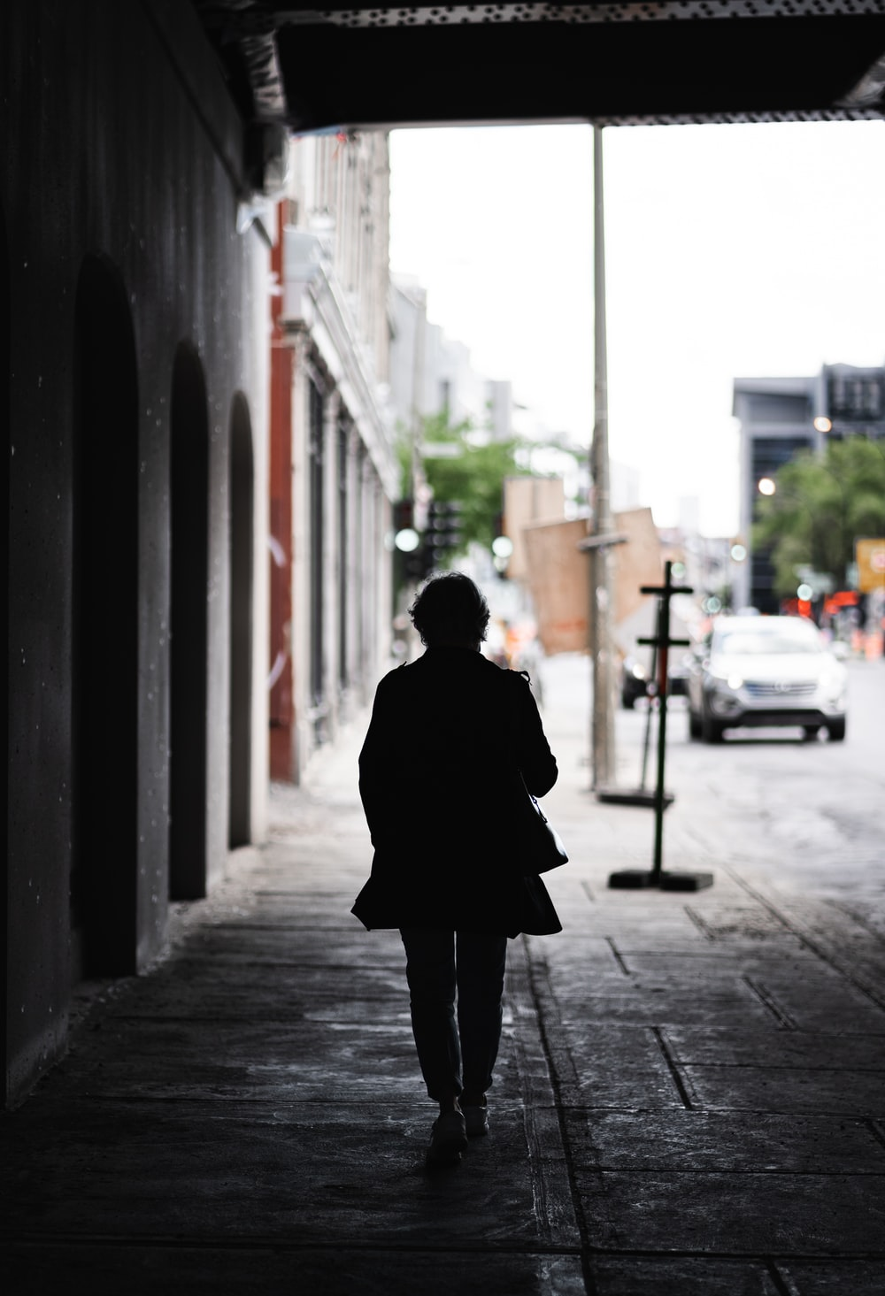 person in black coat standing on sidewalk during daytime