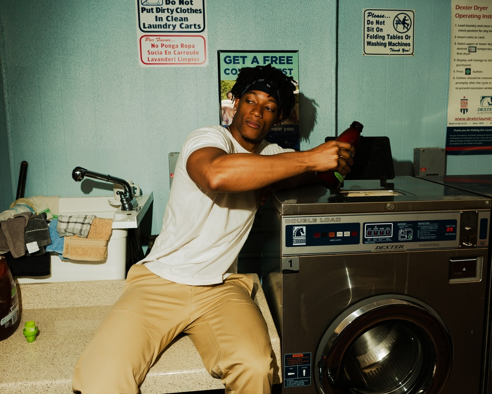 man in white t-shirt and beige pants sitting on front load washing machine