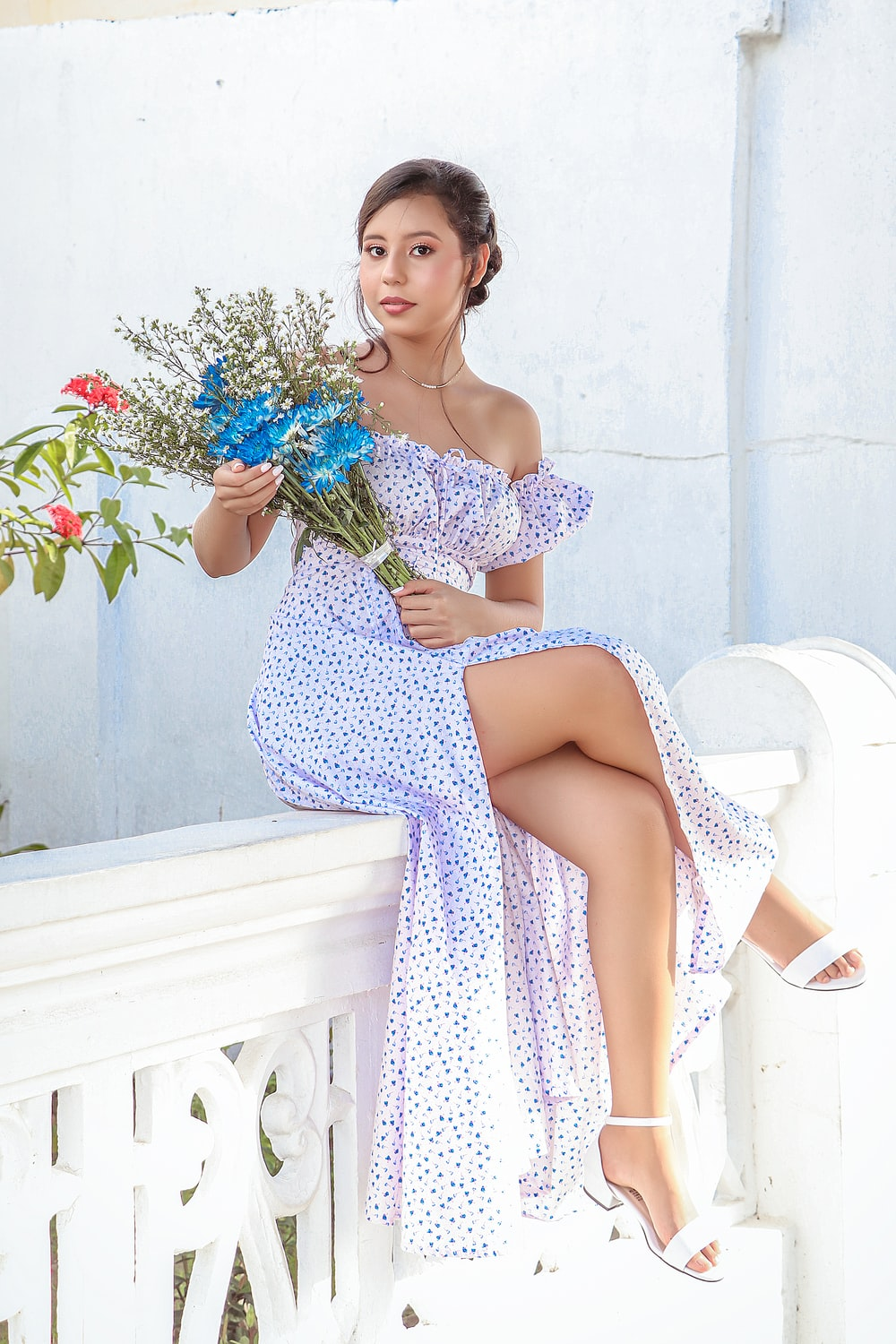 woman in white and black polka dot spaghetti strap dress holding blue flowers