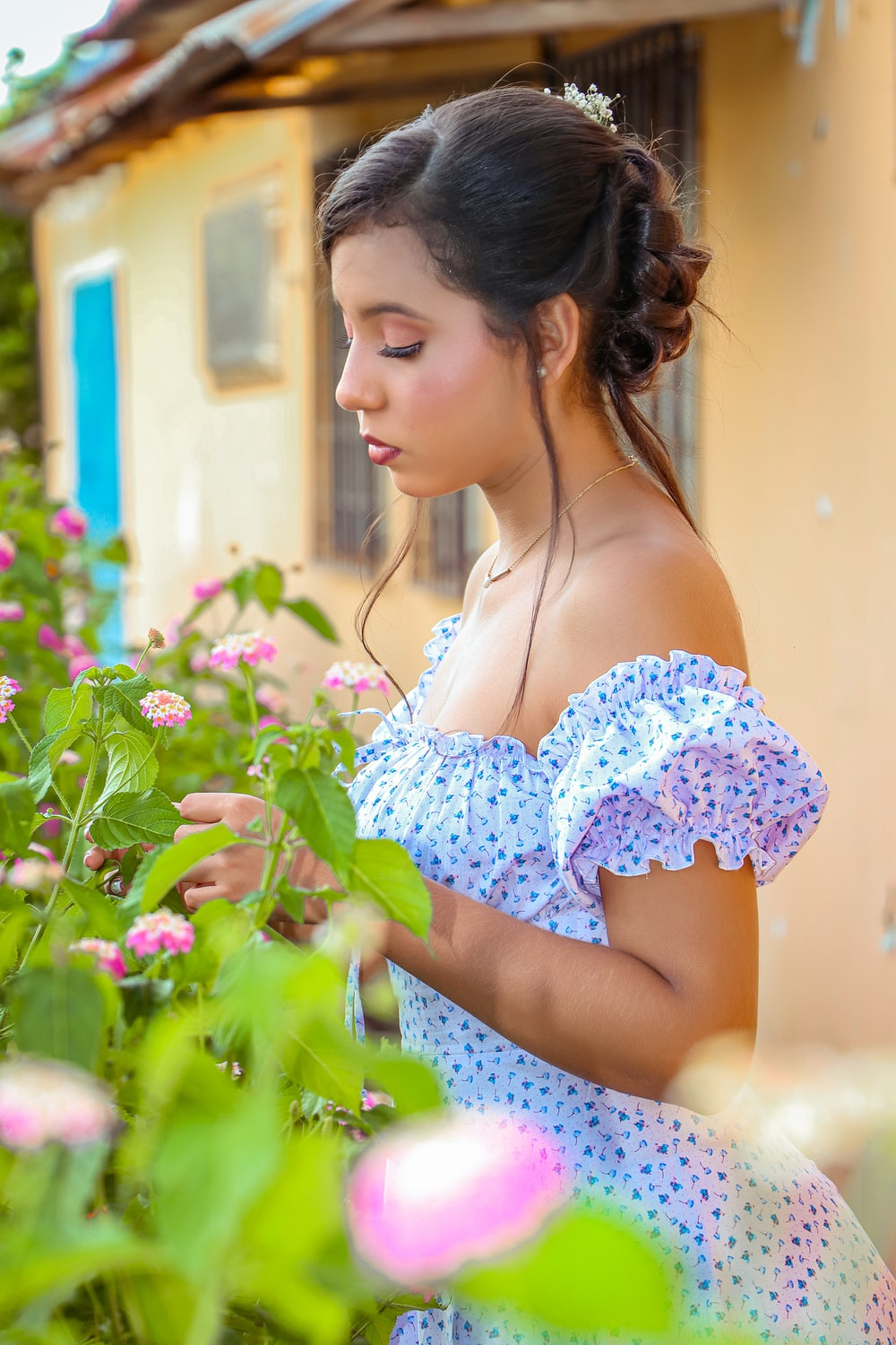 woman in white and blue floral dress standing near pink flowers during daytime