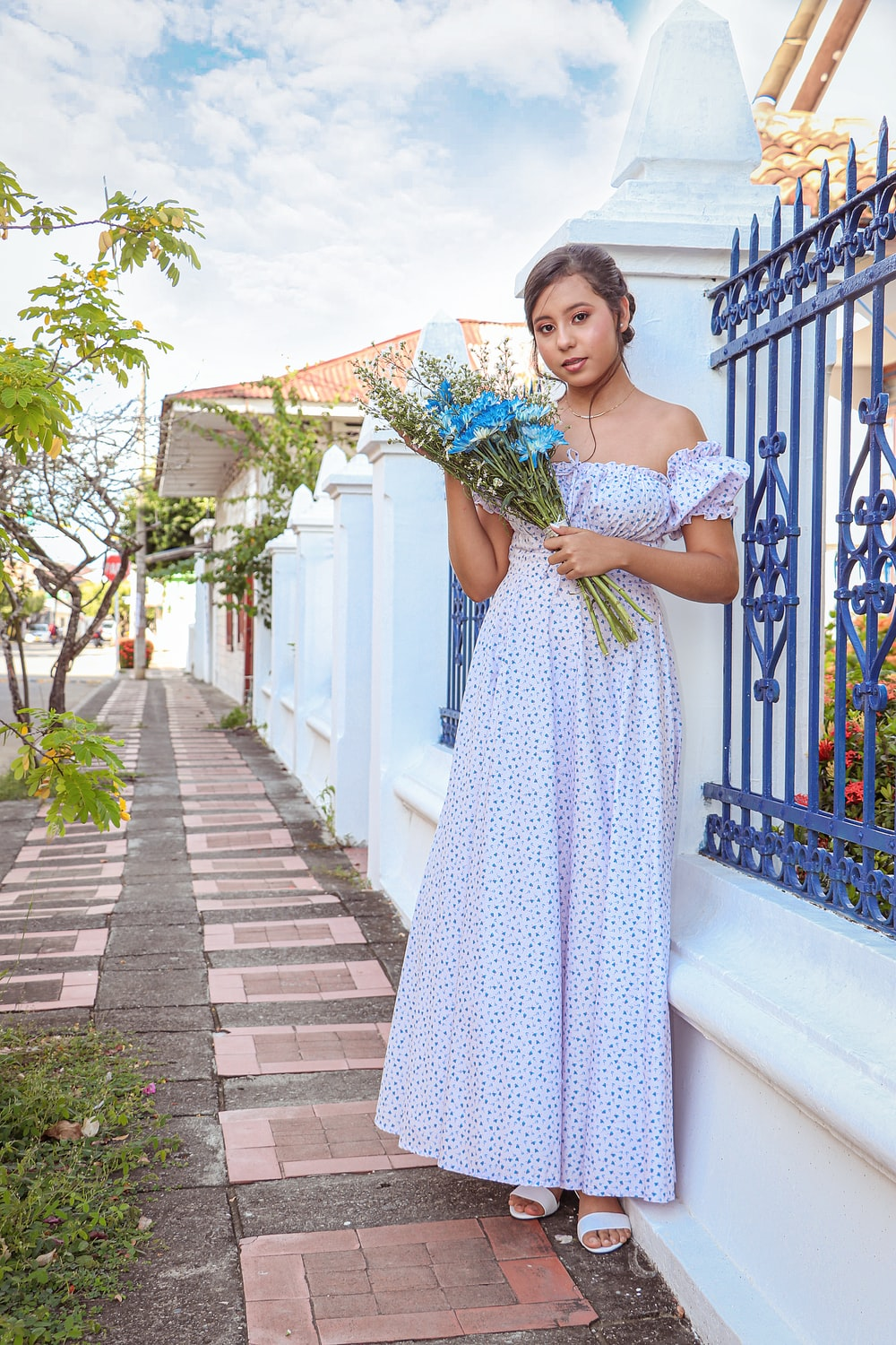 woman in blue and white polka dot sleeveless dress holding bouquet of flowers