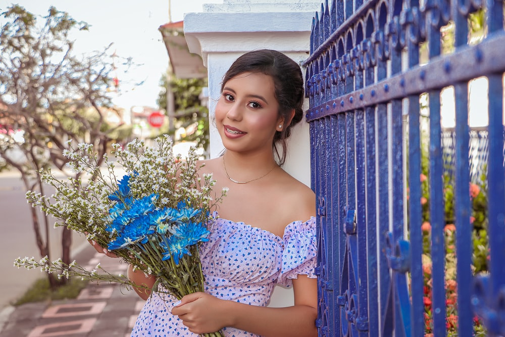 woman in blue and white floral off shoulder dress holding blue flowers