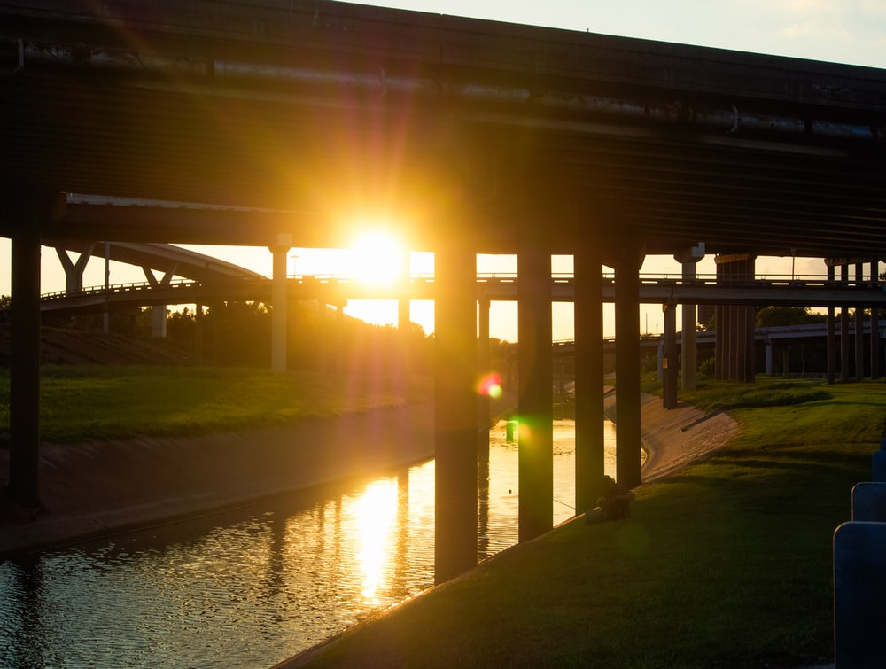brown wooden bridge over river during sunset