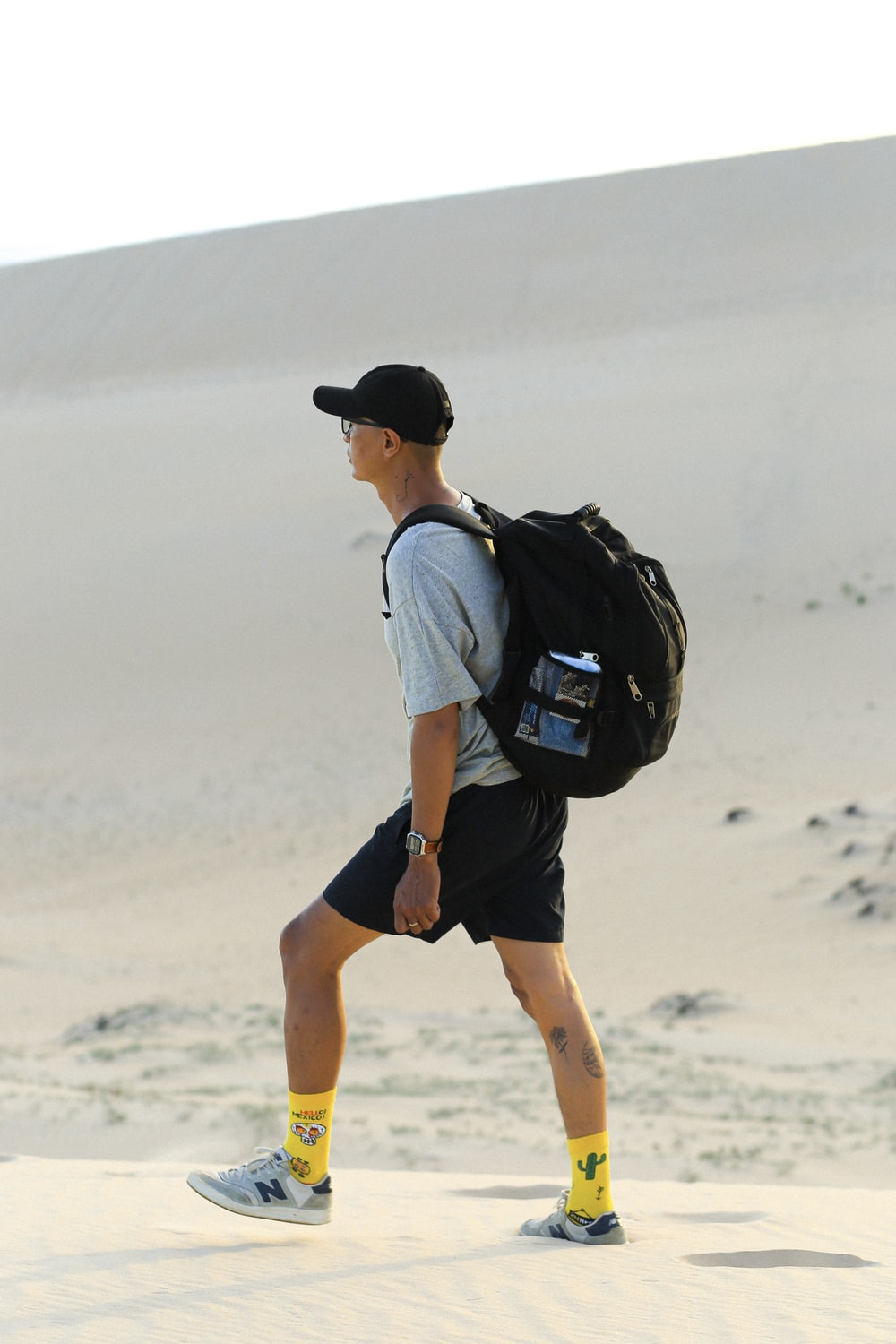 man in white t-shirt and black shorts with black backpack walking on white sand during