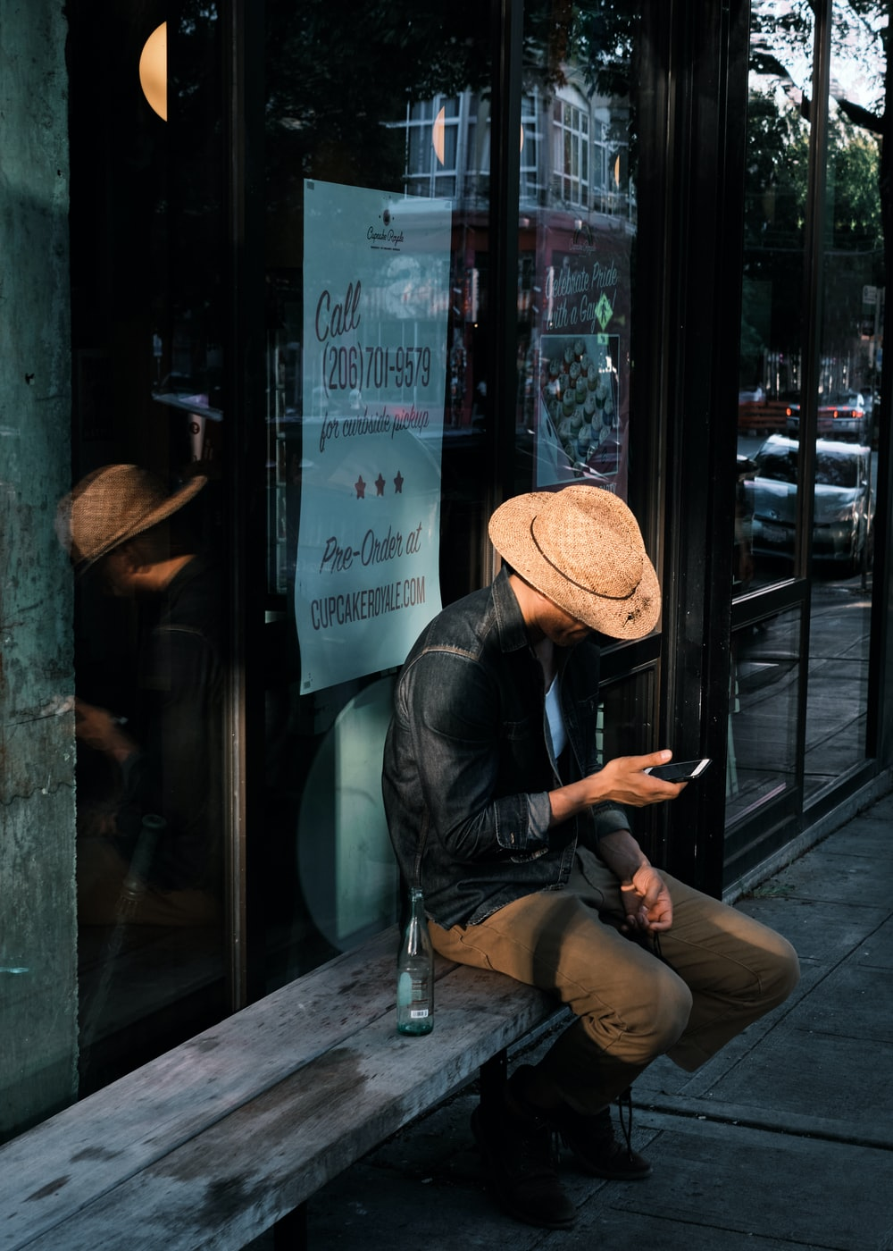 man in black leather jacket and brown fedora hat sitting on chair