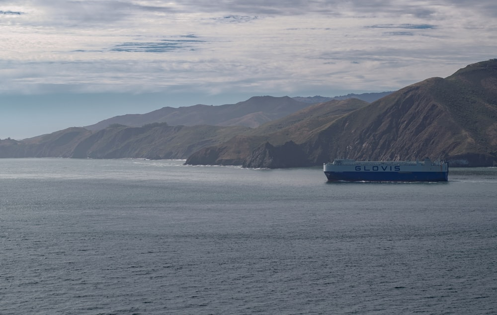 blue and white ship on sea near mountain under white clouds during daytime