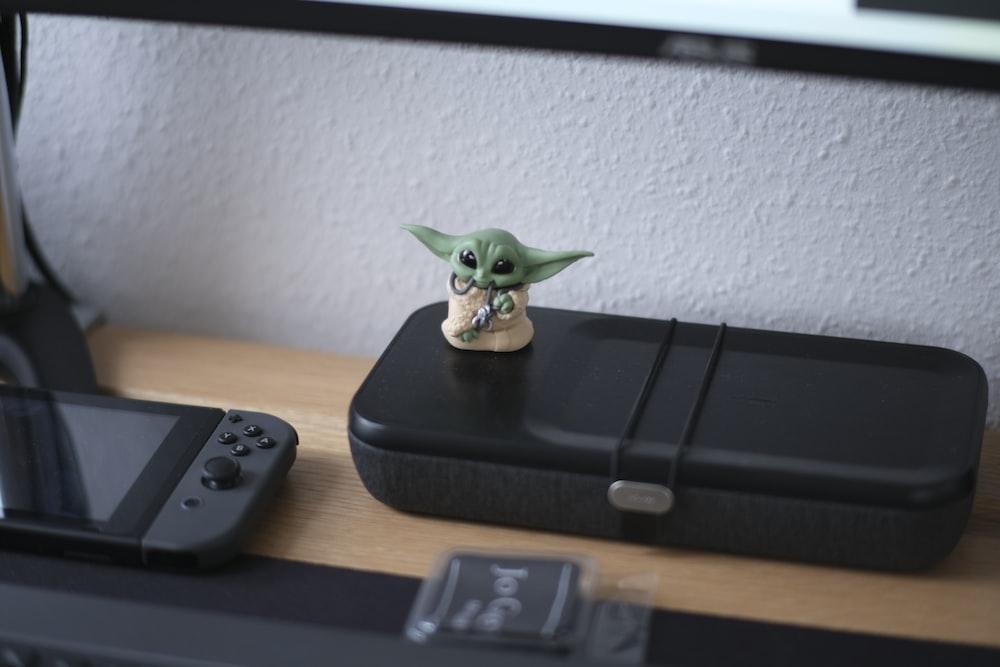 green frog figurine on black device