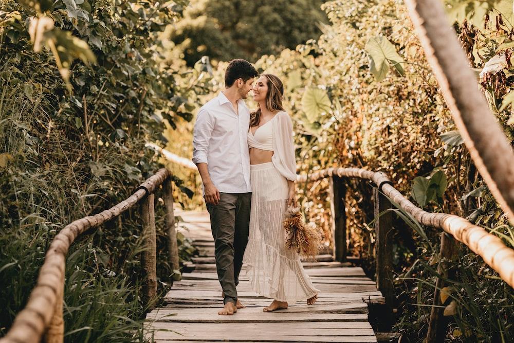 man and woman walking on wooden bridge during daytime