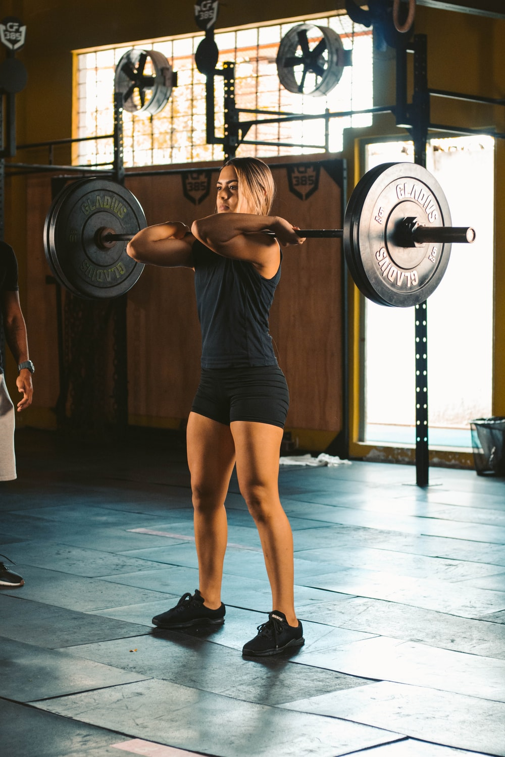 woman in black tank top and black shorts holding black barbell