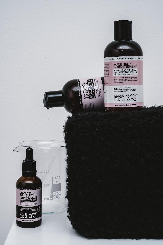 black and white bottle on black textile