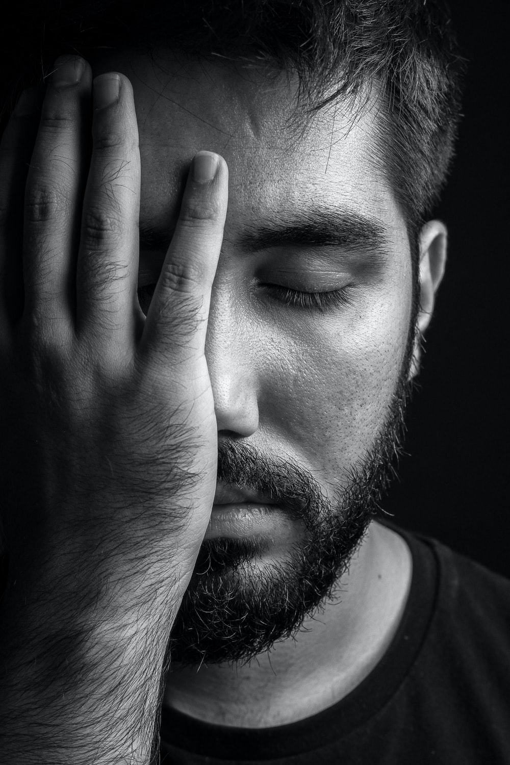 grayscale photo of man covering his face