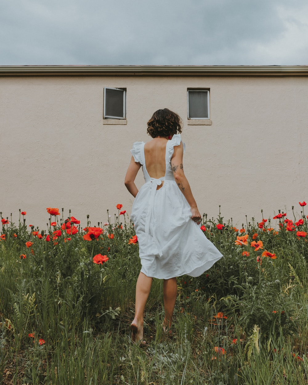woman in white dress standing in front of red flowers
