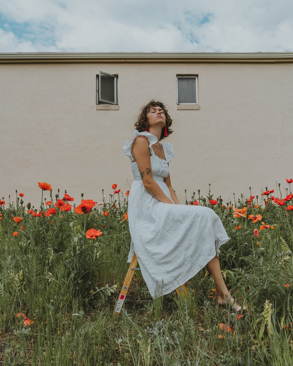 woman in white dress sitting on red flower field during daytime