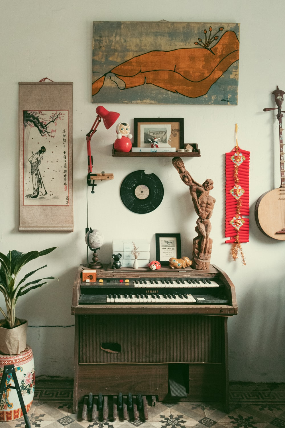 brown wooden upright piano with assorted items on top