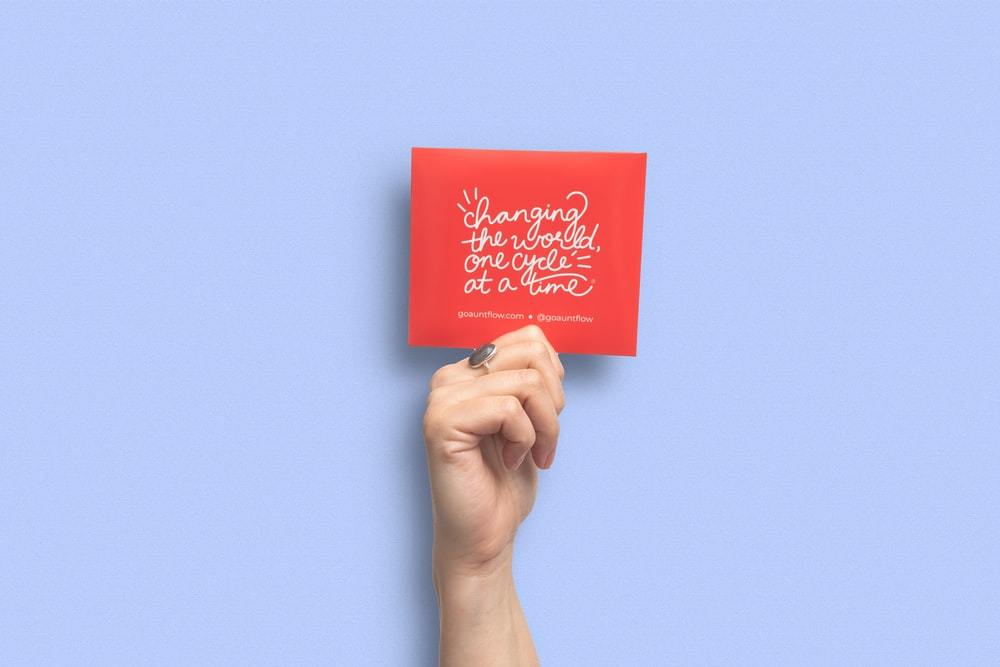 person holding red and white card
