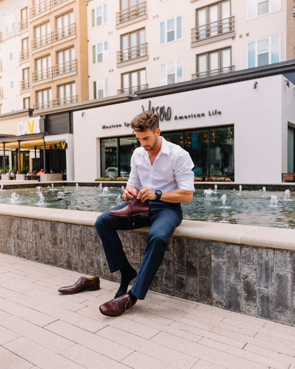 man in white dress shirt and blue denim jeans sitting on concrete bench near water fountain