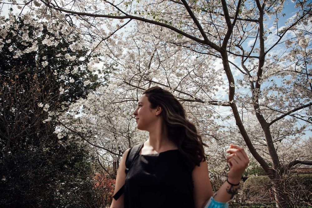 woman in black tank top standing under white cherry blossom tree during daytime