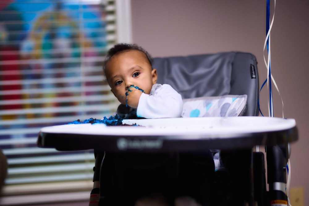 baby in white long sleeve shirt sitting on white high chair
