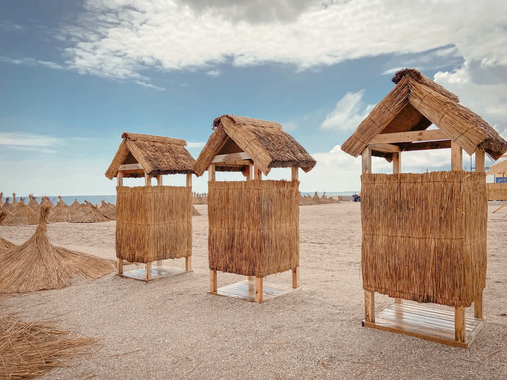 brown wooden houses on beach shore during daytime