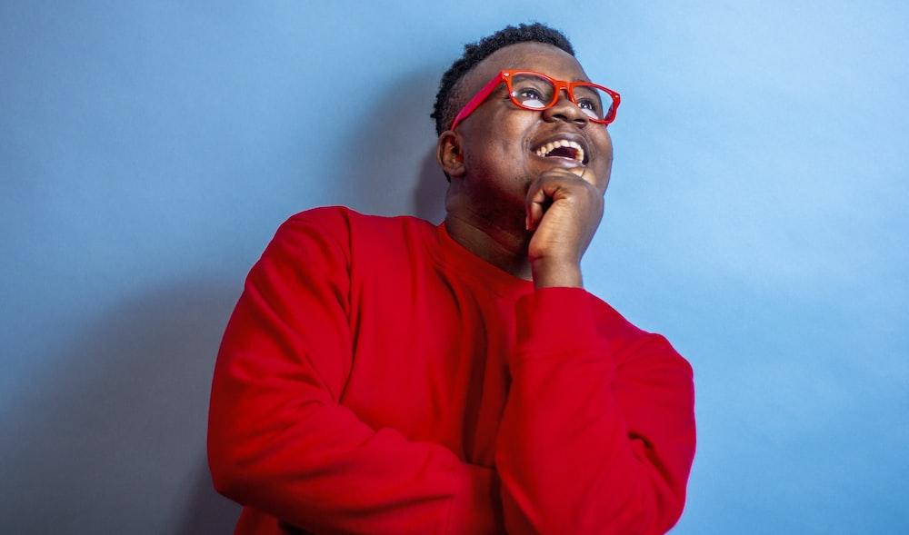 man in red sweater wearing black framed eyeglasses