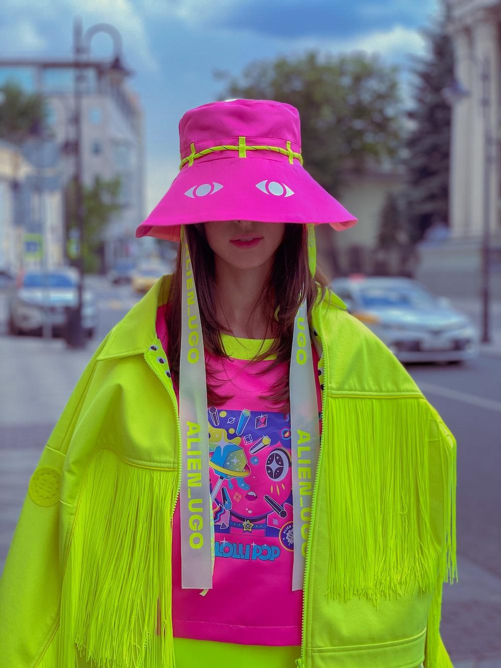 woman in green jacket wearing pink hat