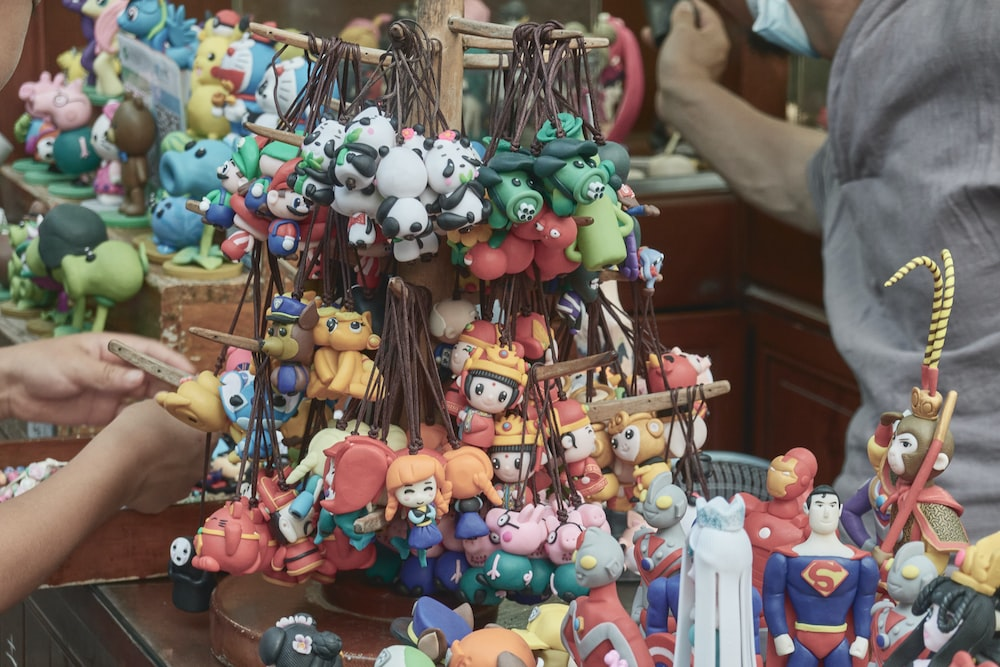 assorted plastic toys on brown wooden rack